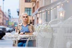 Портрет привлекательной белокурой женщины смотря отсутствующий пока остатки после работы на цифровой таблетке во время времени во Стоковое Изображение