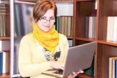Портрет привлекательной девушки с компьтер-книжкой против книжных полок Стоковая Фотография RF
