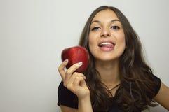 Портрет привлекательной девушки усмехаясь с красным яблоком в ее плодоовощ руки здоровом стоковые изображения