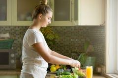 Портрет привлекательной женщины делая свежий салат на kitche Стоковые Фотографии RF
