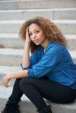 Портрет привлекательной женщины при вьющиеся волосы сидя outdoors стоковые изображения rf