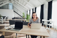 Портрет привлекательной женщины сидя на таблице при портативный компьютер держа телефон и смотря прочь ищущ для Стоковые Фото