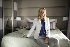 Портрет привлекательной коммерсантки сидя на кровати Стоковая Фотография