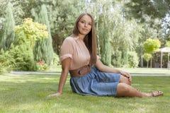 Портрет привлекательной молодой женщины сидя на траве в парке Стоковое Изображение RF