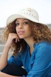Портрет привлекательной молодой женщины сидя outdoors с шляпой Стоковое фото RF