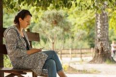 Портрет привлекательной молодой кавказской женщины сидя на стенде снаружи с мобильным телефоном Стоковые Фотографии RF