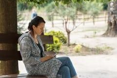 Портрет привлекательной молодой кавказской женщины сидя на стенде снаружи с мобильным телефоном Стоковые Изображения RF