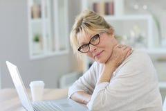 Портрет причудливой старшей женщины работая на компьтер-книжке Стоковое Фото