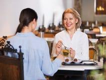 Портрет 2 приятных женщин с чаем и шоколадами Стоковые Изображения