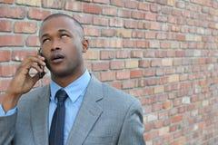 Портрет пробуренного бизнесмена говоря на мобильном телефоне против предпосылки кирпичной стены Стоковые Изображения RF