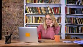 Портрет пробуренной и надоеданной кавказской девушки с прокалывая деятельностью с ноутбуком на предпосылке книжных полка акции видеоматериалы