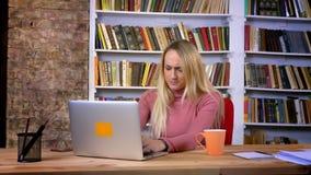 Портрет пробуренной кавказской девушки с прокалывая деятельностью с ноутбуком и зевать на предпосылке книжных полка видеоматериал