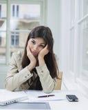 Портрет пробуренной коммерсантки сидя на столе в офисе Стоковое Фото