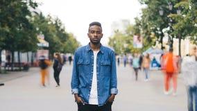Портрет промежутка времени персоны симпатичного Афро-американского человека сиротливой стоя в пешеходной улице и смотря сток-видео
