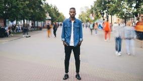 Портрет промежутка времени подавленного Афро-американского человека смотря камеру стоя самостоятельно в улице, руках в карманн видеоматериал