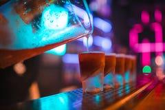 Портрет профессионального бармена лить спиртное digestif в стопках на баре стоковое фото