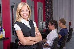 Портрет профессионального парикмахера представляя в салоне красоты стоковые фото