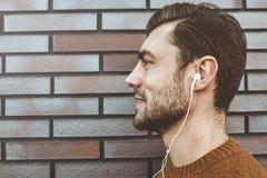 Портрет профиля жизнерадостного молодого человека, слушая музыку в шлемофоне на мобильном телефоне Одетый в модных одеждах outdoo стоковое изображение
