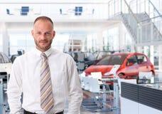 Портрет продавца автомобилей в выставочном зале Стоковое Изображение