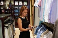 Портрет продавца молодой женщины используя сенсорную панель для того чтобы проверить цены для одежд пока стоящ в магазине моды Стоковое Изображение