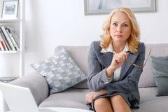 Портрет психолога женщины сидя на вскользь домашнем офисе смотря камеру серьезную стоковое изображение