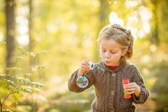 Портрет пузырей мыла смешной симпатичной маленькой девочки дуя Милая белокурая голубоглазая девушка в желтом связанном пальто в стоковые изображения rf
