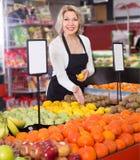 Портрет плодоовощей зрелой белокурой женщины предлагая в бакалее стоковая фотография