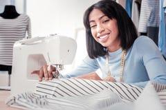 Портрет работающий на самого себя портноя с швейной машиной стоковые фото
