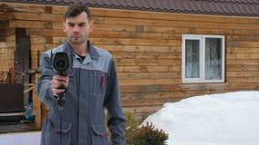 Портрет работника дома который уносит осмотр термальным imager Искать потери  акции видеоматериалы