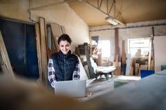 Портрет работника женщины с компьтер-книжкой в мастерской плотничества Стоковое Изображение