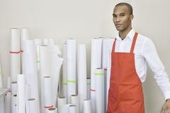 Портрет работника печатного станка стоя с бумагой свертывает в предпосылке Стоковое фото RF