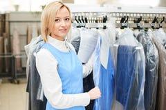 Портрет работника прачечной девушки на предпосылке пальто кладет на полку стоковая фотография rf
