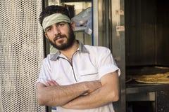 Портрет работника хлебопекарни стоя перед магазином хлебопекарни Стоковые Фото