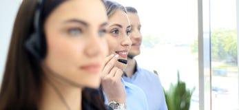 Портрет работника центра телефонного обслуживания сопровоженный ее командой Усмехаясь оператор работы с клиентом на работе Стоковое фото RF