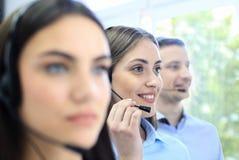 Портрет работника центра телефонного обслуживания сопровоженный ее командой Усмехаясь оператор работы с клиентом на работе Стоковое Изображение RF