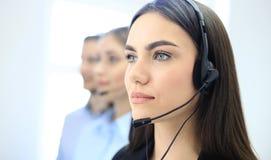 Портрет работника центра телефонного обслуживания сопровоженный ее командой Усмехаясь оператор работы с клиентом на работе Стоковые Изображения RF