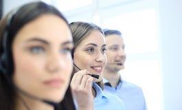 Портрет работника центра телефонного обслуживания сопровоженный ее командой Усмехаясь оператор работы с клиентом на работе Стоковые Изображения