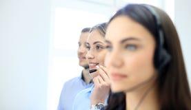 Портрет работника центра телефонного обслуживания сопровоженный ее командой Усмехаясь оператор работы с клиентом на работе Стоковые Фото