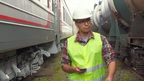 Портрет работника человека железной дороги, идет к железнодорожному вокзалу сток-видео