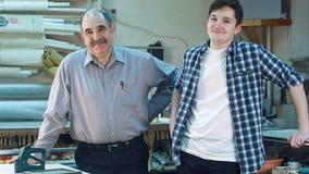 Портрет 2 работников, стоящ в мастерской, усмехающся и смотрящ камеру Стоковая Фотография