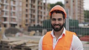Портрет рабочий-строителя в оранжевом шлеме усмехаясь на камере Построитель стоит против фона a видеоматериал