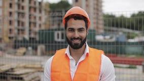 Портрет рабочий-строителя в оранжевом шлеме усмехаясь на камере Построитель стоит против фона a сток-видео