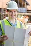 Портрет рабочий-строителя на строительной площадке смотря планы дома стоковое изображение rf