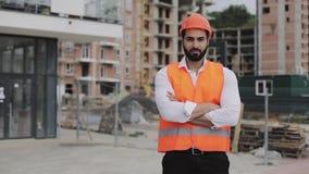 Портрет рабочий-строителя на строительной площадке с пересеченными руками смотря камеру Профессии, конструкция видеоматериал