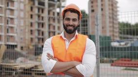 Портрет рабочий-строителя на строительной площадке с пересеченными руками смотря камеру Профессии, конструкция акции видеоматериалы
