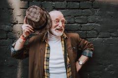 Портрет радостного старика peeking вне его шляпа стоковые фотографии rf