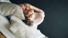 Портрет радостной девушки при стекла короткого вьющиеся волосы нося свертывая в кровати, усмехаясь и смотря выражать камеры сток-видео