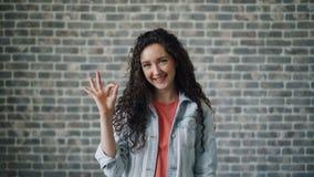 Портрет радостной молодой дамы показывая жест рукой ОК усмехаясь смотрящ камеру акции видеоматериалы