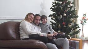 Портрет радостной семьи обнимая сидеть с трутнем на кожаном стуле около рождественской елки семья принципиальной схемы счастливая сток-видео
