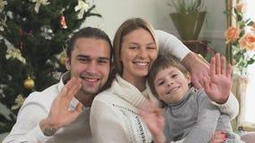 Портрет радостной семьи обнимая усаживание на предпосылке рождественской елки дома семья принципиальной схемы счастливая сток-видео